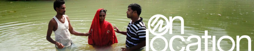 woman in India being baptized in a river