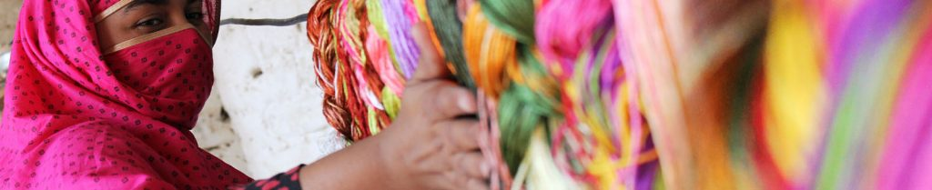 Woman wearing a niqab working with colorful yarns
