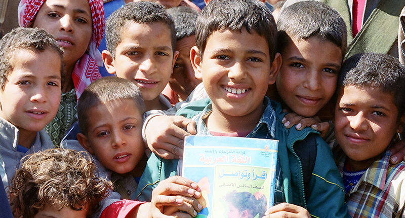 group of smiling boys in middle eastern country